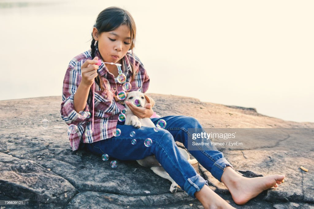 Girl Blowing Bubbles While Sitting With Puppy On Rock Against Lake : Stock Photo