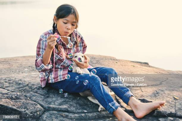 Girl Blowing Bubbles While Sitting With Puppy On Rock Against Lake