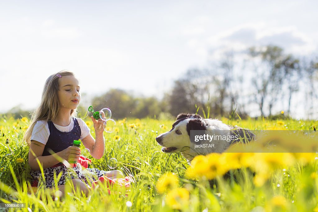 Girl blowing bubbles with dog in field : Stock Photo