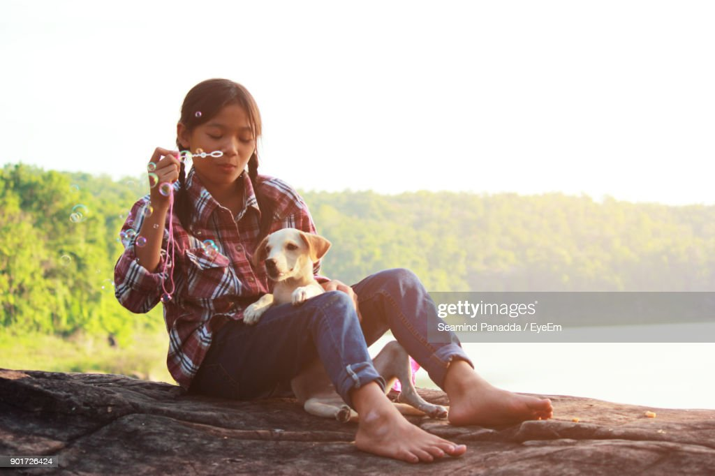 Girl Blowing Bubbles With Dog Sitting On Rock Against Lake : Stock Photo