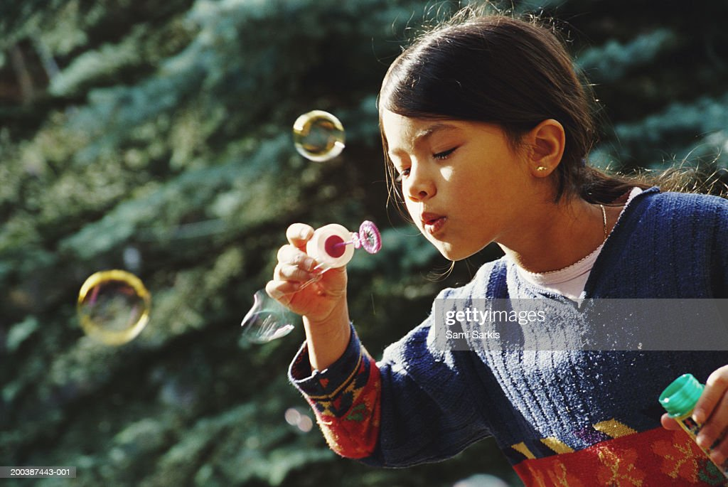 Girl (7-9) blowing bubble-wand, outdoors : Stock Photo
