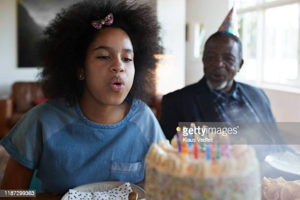 girl blowing candles during birthday party - rite of passage stock pictures, royalty-free photos & images