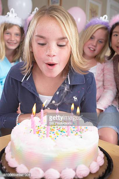 girl (10-11 years) blowing candles on birthday cake, four friends sitting behind, elevated view - 10 11 years stock pictures, royalty-free photos & images