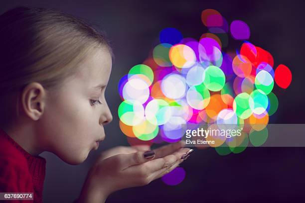 Girl blowing colorful lights of bokeh