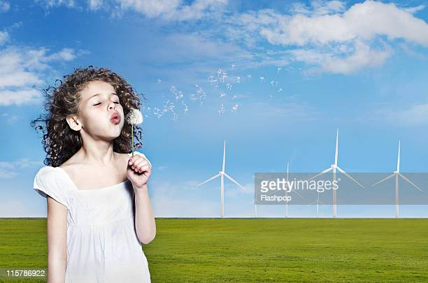 girl blowing dandelion clock on wind farm - newpremiumuk stock pictures, royalty-free photos & images