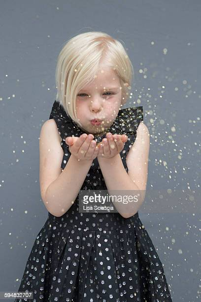 Girl blowing glitter against gray background