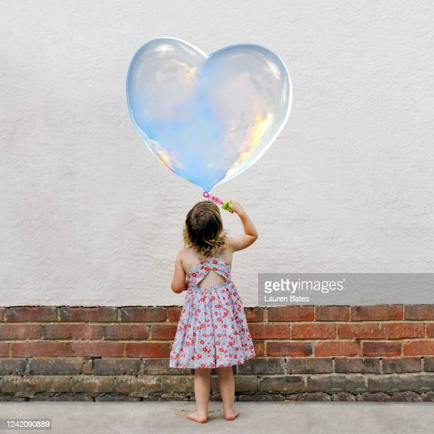 girl blowing heart bubbles - girls stock pictures, royalty-free photos & images