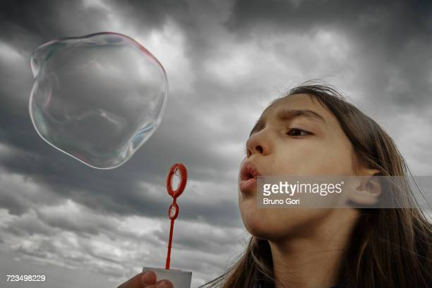 Girl blowing large soap bubble