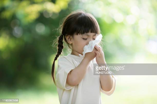 girl blowing nose outdoors - ティッシュ ストックフォトと画像