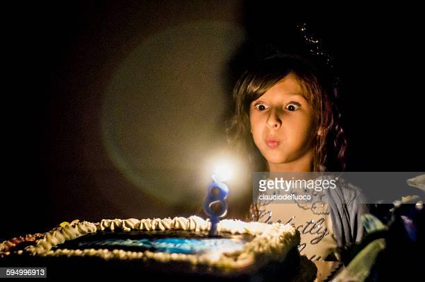 Girl blowing on the birthday's cake candle