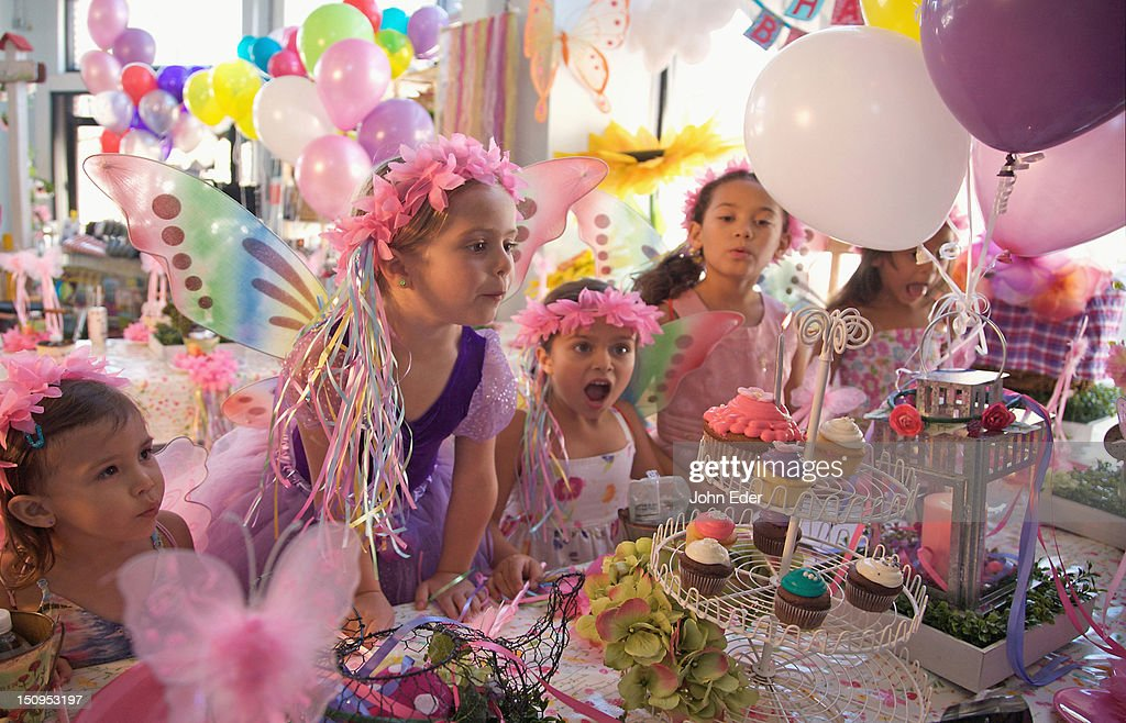 Girl blowing out birthday candle : Stock Photo