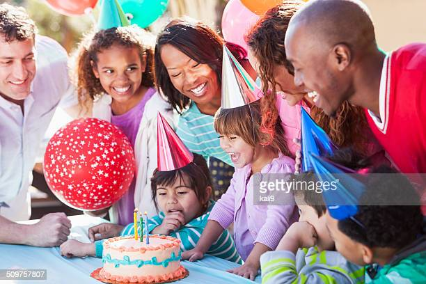 girl blowing out birthday candles - birthday balloons stock photos and pictures