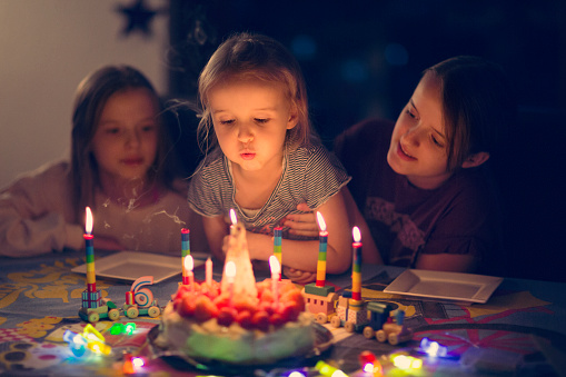 Girl blowing out candles on a birthday cake in low lighting - gettyimageskorea