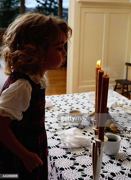 Girl Blowing Out Candles on a Table