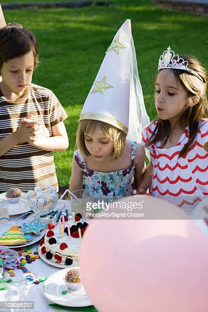 girl blowing out candles on birthday cake at outdoor birthday party - asian style conical hat stock pictures, royalty-free photos & images