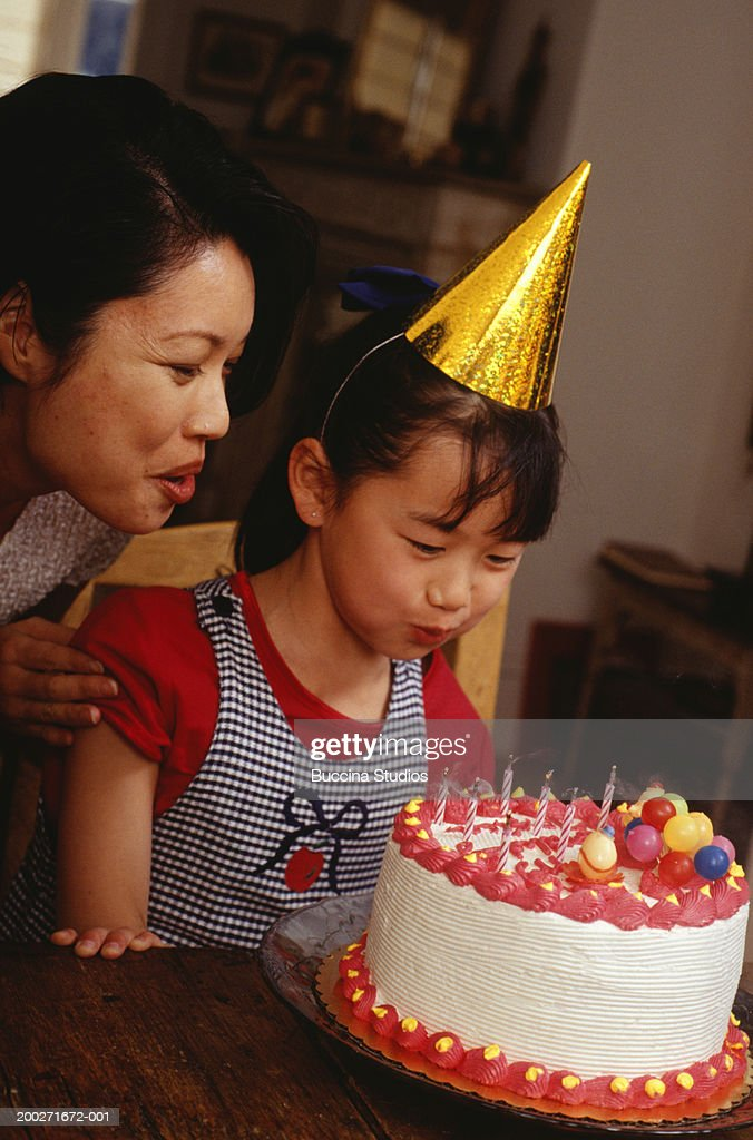 Girl Blowing Out Candles On Birthday Cake In Living Room Stock Photo