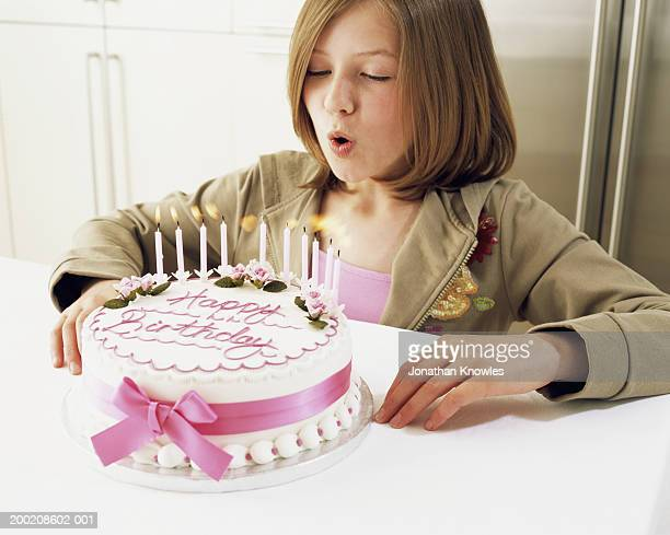 Girl (10-12) blowing out candles on birthday cake