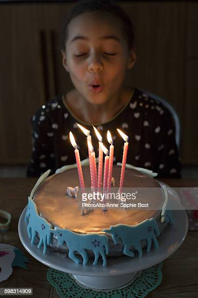 girl blowing out candles on birthday cake - girl blowing horse stock pictures, royalty-free photos & images