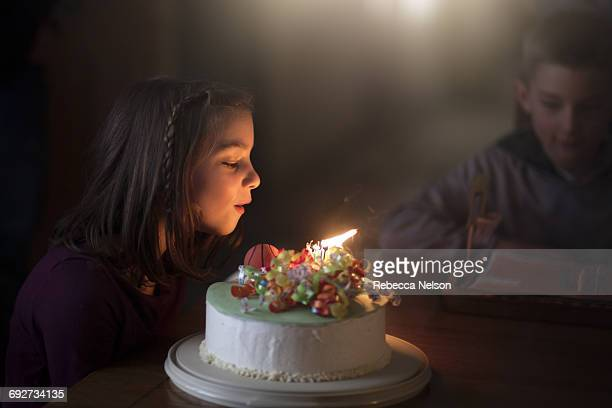 girl blowing out candles on birthday cake - birthday candles stock photos and pictures