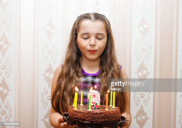 Girl blowing out candles on her birthday cake