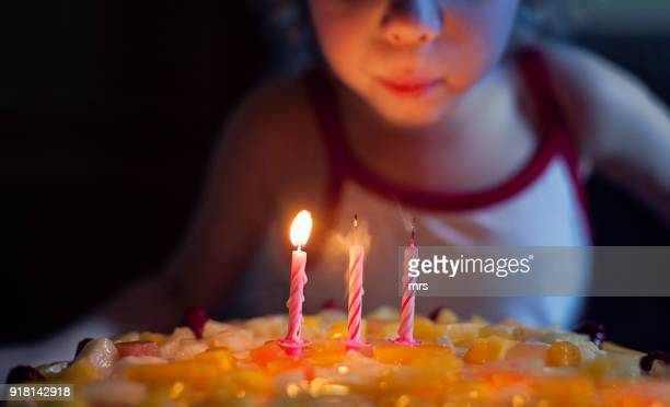 girl blowing out candles on her birthday cake - soplar fotografías e imágenes de stock
