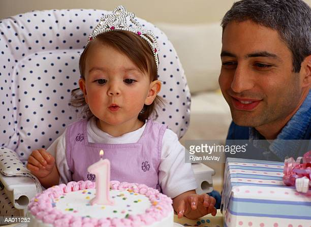 Girl Blowing Out Her First Birthday Candle