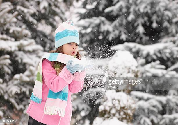 Girl Blowing Pile of Snow Out of Hands