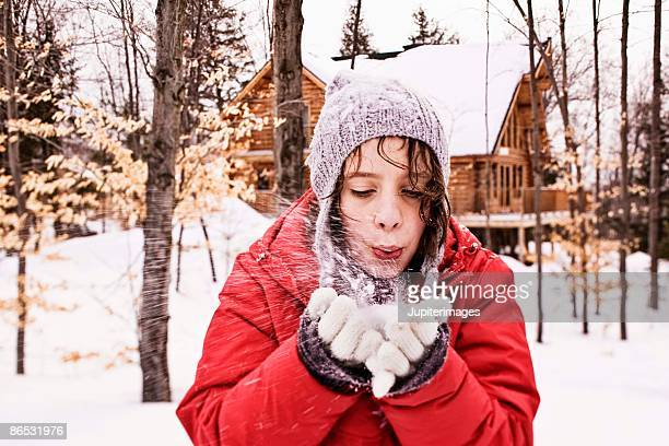 Girl blowing snow from hands