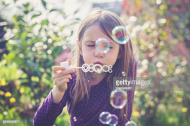 Girl blowing soap bubbles in a garden