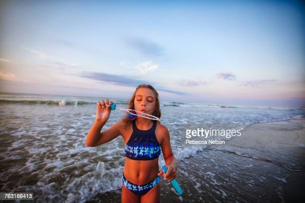 girl blowing soap bubbles on beach - rebecca nelson stock pictures, royalty-free photos & images