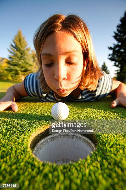 girl blows ball into hole - blue balls pics stock pictures, royalty-free photos & images