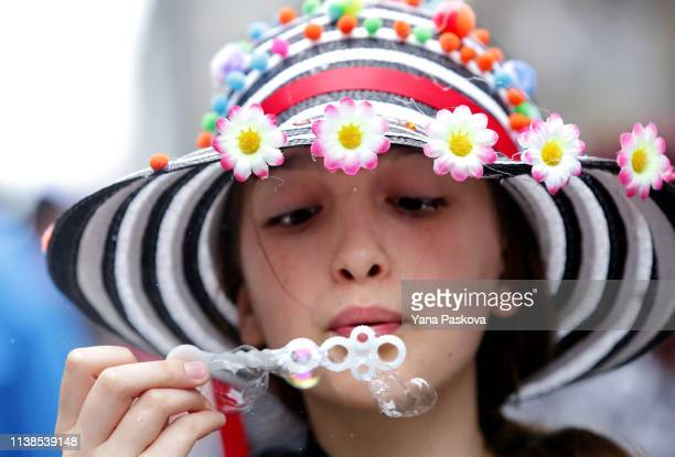 A girl blows bubbles as people gather in Midtown East for the annual Easter Parade on April 21 2019 in New York City Each year New Yorkers put on...
