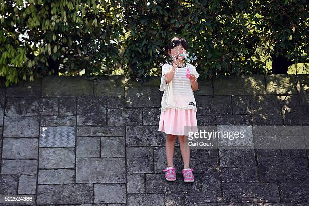 Girl blows bubbles as she waits at an evacuation centre following an earthquake, on April 20, 2016 in Mashiki near Kumamoto, Japan. As of April 20,...