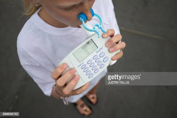 A girl blows into a spirometer during a photocall to promote clean air in central London on September 2 2016 A Spirometer device measures the volume...