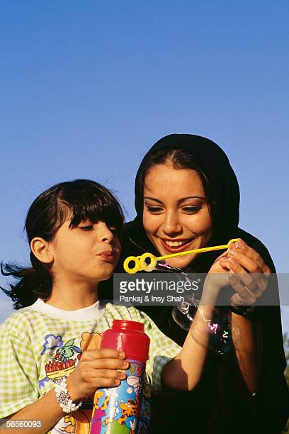 A Girl blows off the soap bubble while the mother holds her hand.