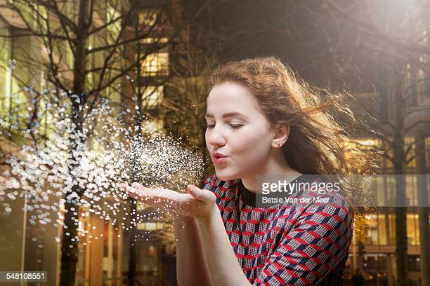girl blows stardust from hand in city at night. - soffiare foto e immagini stock