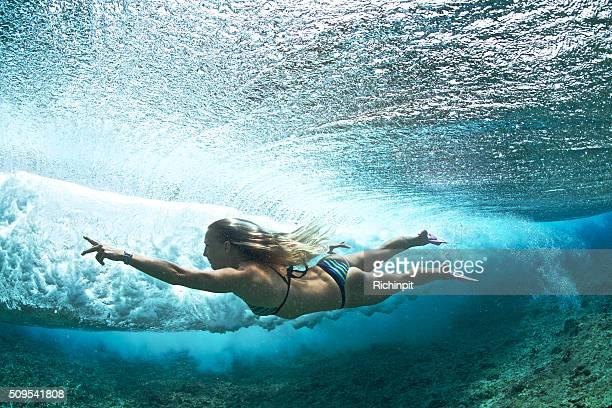 Girl bodysurfs behind a breaking wave