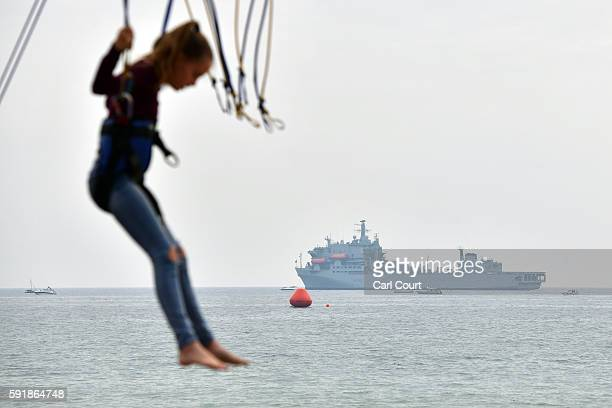 A girl bounces on a fairground ride as RFA Argus is anchored offshore during the Bournemouth Air Festival on August 18 2016 in Bournemouth England...