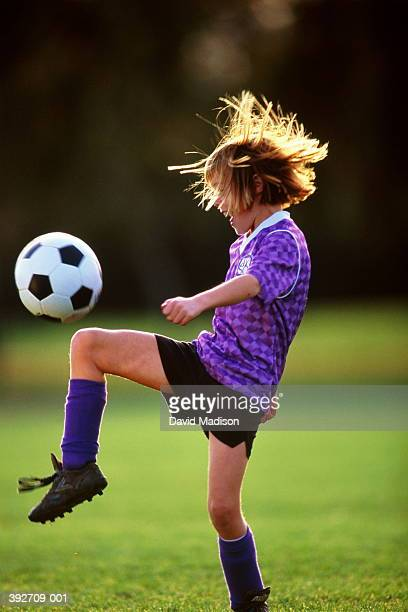 Girl (6-8) bouncing football on knee