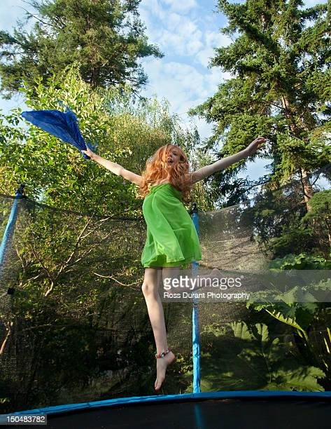 a girl bouncing on a trampoline in a garden - barefoot redhead stock photos and pictures