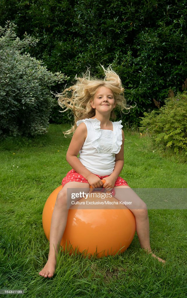 Girl bouncing on ball in meadow : Stock Photo