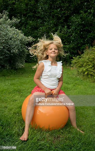 Girl bouncing on ball in meadow