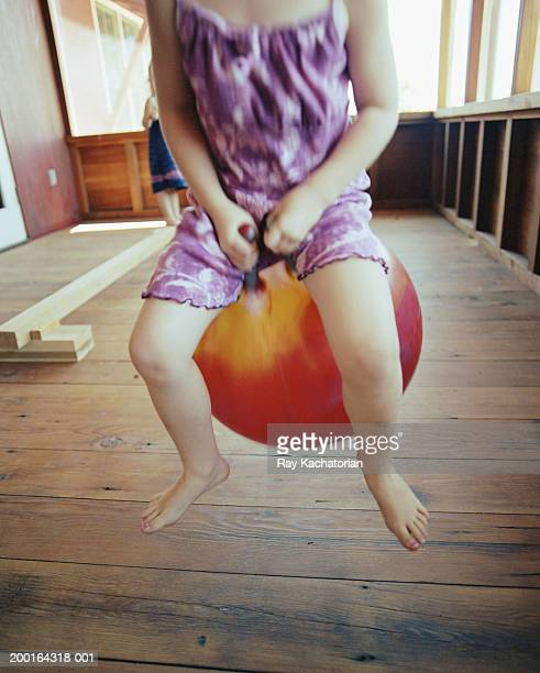 Girl (9-11) bouncing on ball, low section