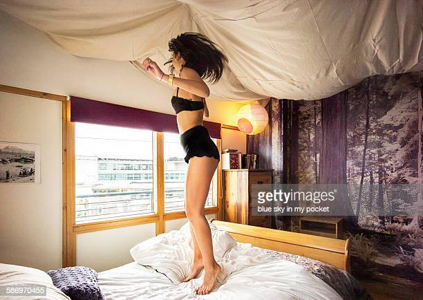 A girl bouncing on the bed