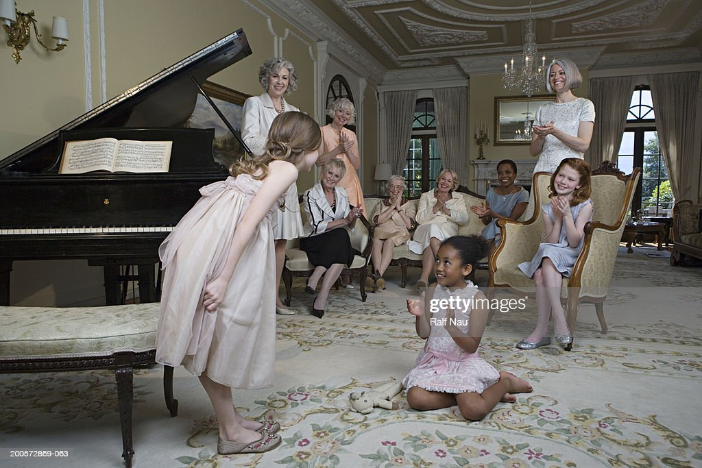 Girl (6-8) bowing by piano at party : Stock Photo