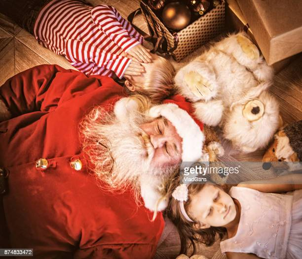 Girl, boy and santa lie on the floor