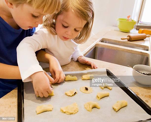 girl, boy preparing cookies for baking
