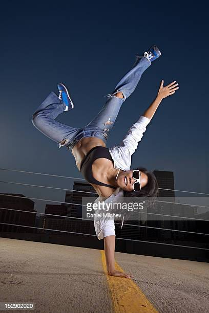 Girl breakdancing on a rooftop.