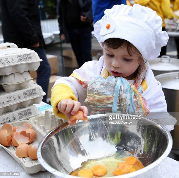 A girl breaks an egg as Members of the World Brotherhood of the Huge Omelet cook giant omlette within a 4 metre diameter frying pan in Malmedy...