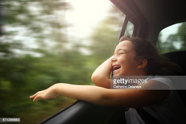 A girl breathing air through the window of a car